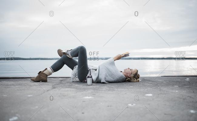 Full length of woman reading diary while lying at lakeshore against sky