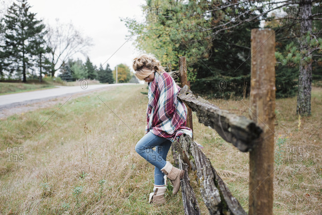 Full length of thoughtful woman standing against wooden fence at field