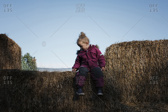 Full length of girl sitting on hay bale against clear sky