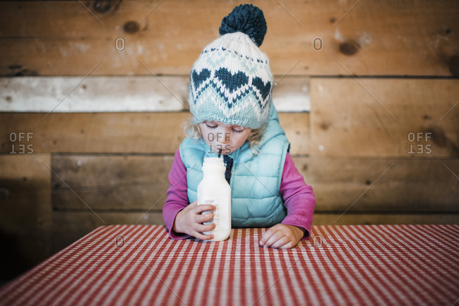 Girl wearing warm clothing while having drink at table