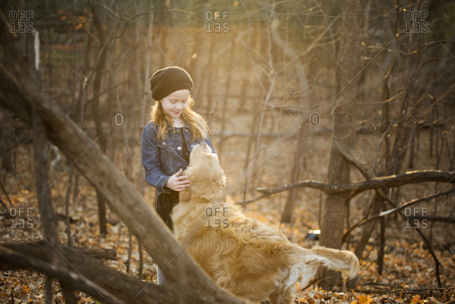 Girl petting dog while standing amidst trees at park