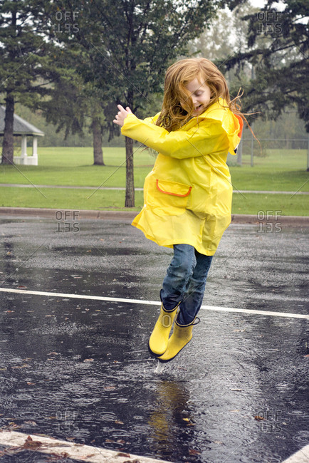 Cheerful girl wearing raincoat while jumping on road during rainfall