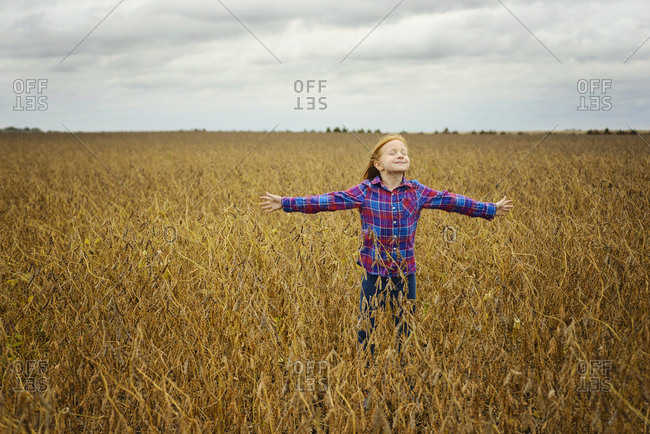Carefree girl with arms outstretched standing amidst soybean's field against cloudy sky