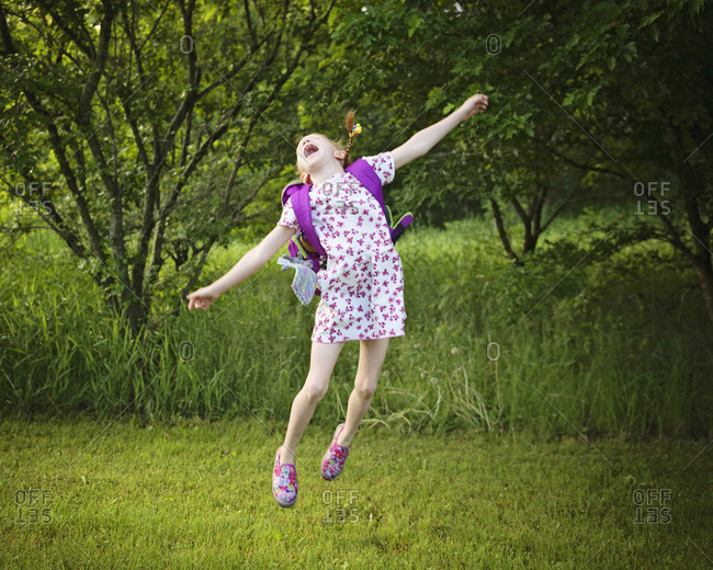 Cheerful girl with backpack jumping over grassy field at park