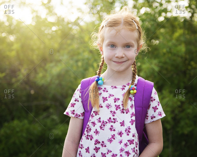 Portrait of confident girl with backpack at park