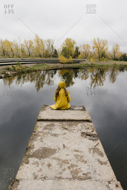 High angle view of thoughtful woman sitting on pier over lake