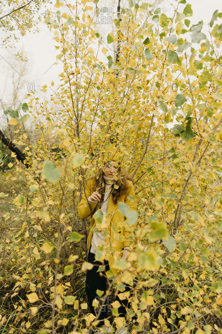 Woman standing amidst plants during autumn
