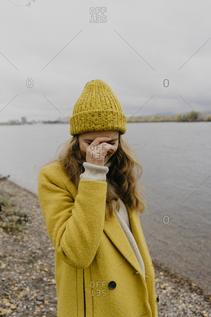 Woman with hand on face wearing winter coat while standing at lakeshore