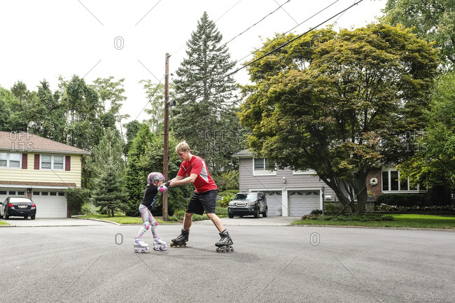 Father teaching daughter to inline skate on road