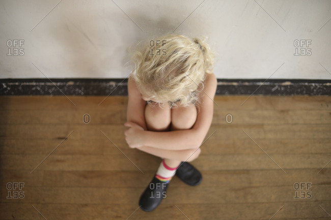 High angle view of depressed girl hugging knees while sitting on floor at home