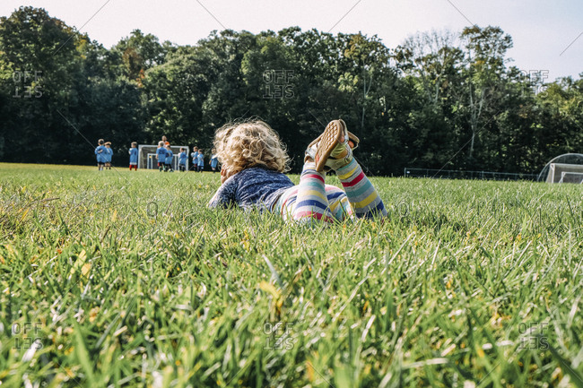 Girl looking at soccer match while lying on grassy field at playground