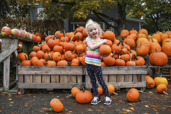 Portrait of playful girl sticking out tongue while holding pumpkin