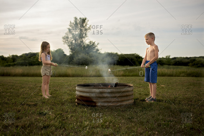 Siblings roasting marshmallows over fire pit