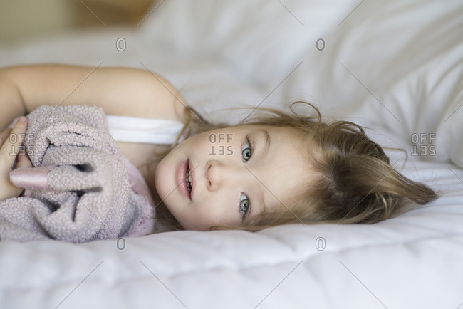 Portrait of cute girl lying on bed