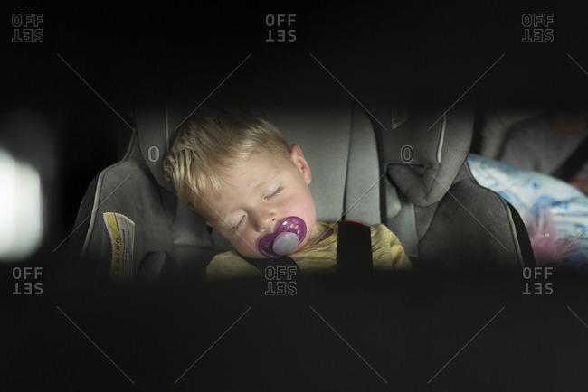 Boy sucking pacifier while sleeping in car