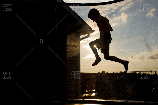 Playful boy jumping on trampoline during sunset