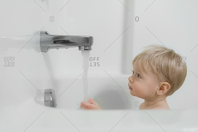 Cute boy looking at water running from faucet at bathroom