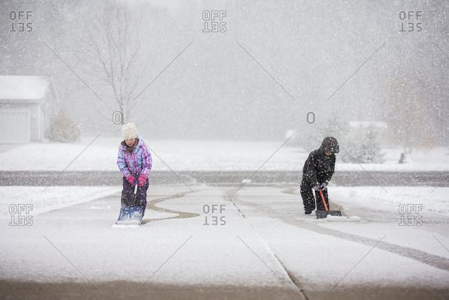 Siblings shoveling snow at driveway during snowfall