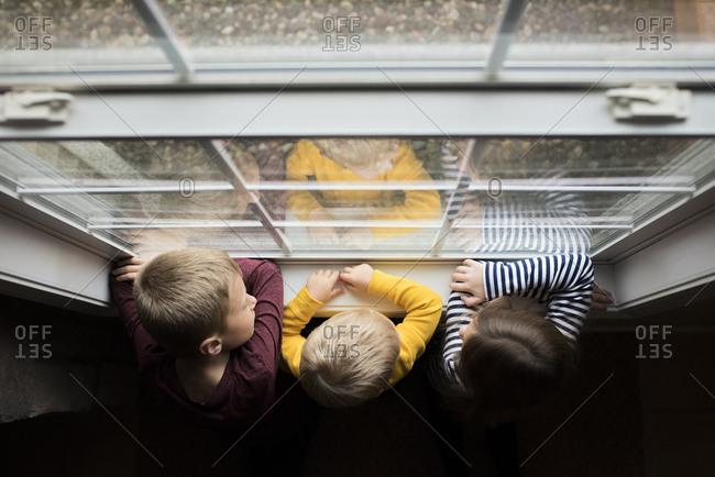 Overhead view of siblings standing by window in darkroom