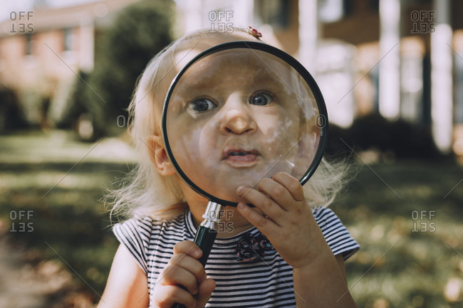 Portrait of playful baby girl with magnifying glass