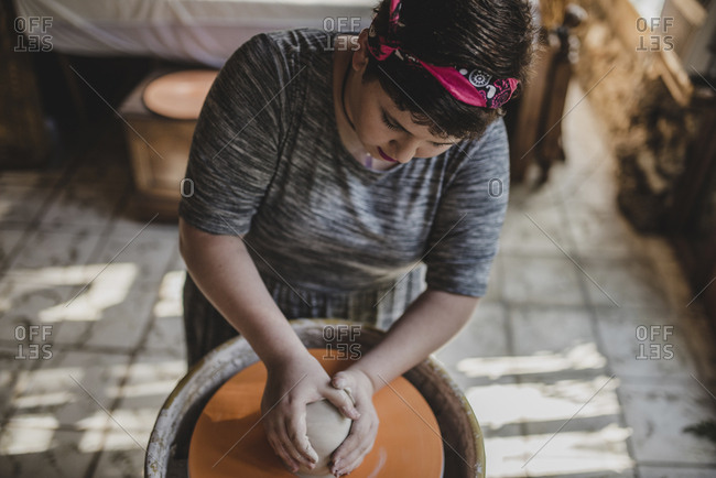 High angle view of female potter making clay pot at pottery