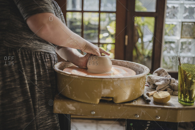 Midsection of potter using pottery wheel at workshop