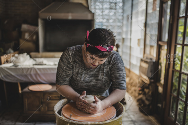 Female craftsperson making clay pot at pottery