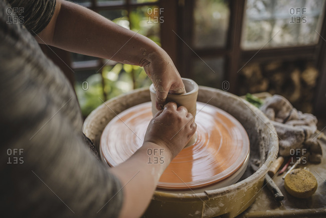 Midsection of craftsperson molding clay on pottery wheel at workshop