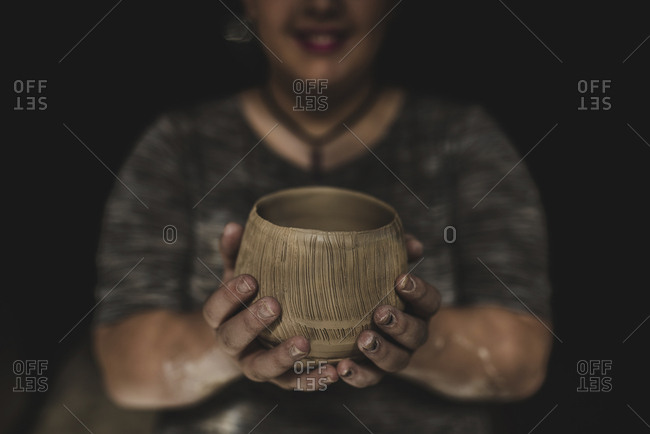 Midsection of potter holding craft product in darkroom