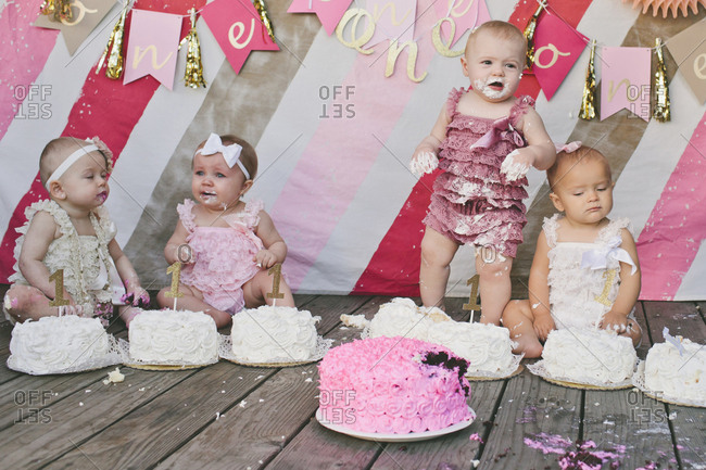 Cute baby girls with birthday cakes on floorboard against decoration at party