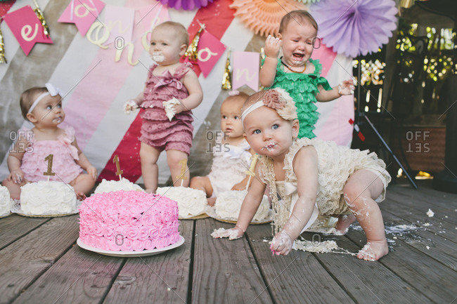 Baby girls with birthday cakes on floorboard