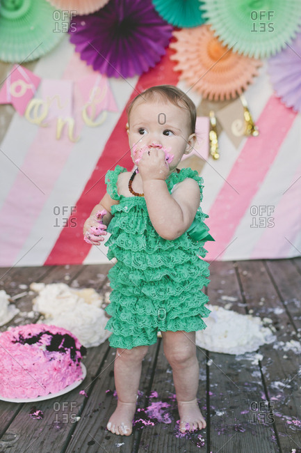 Cute baby girl eating birthday cake while standing on floorboard