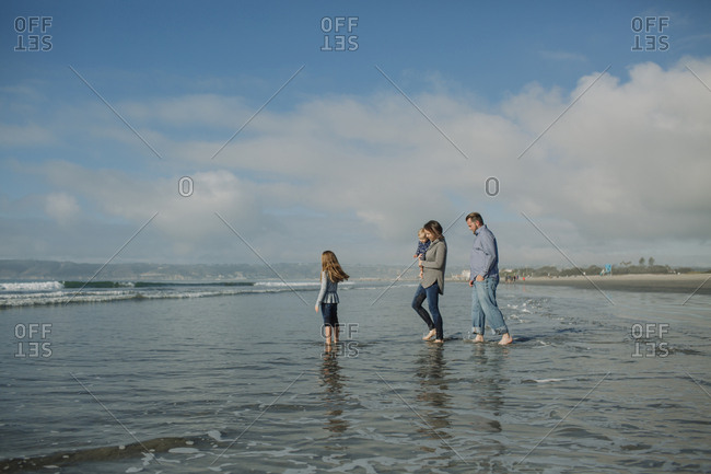 Family in sea against cloudy sky at beach