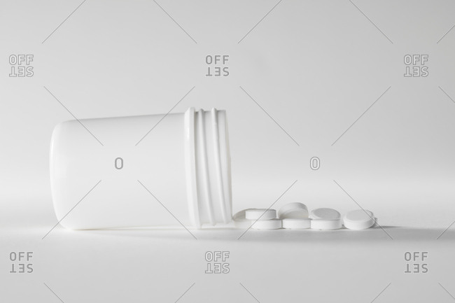 White medicine container with white pills on a white background