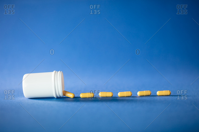 Close up of white medicine bottle with yellow pills on a blue background