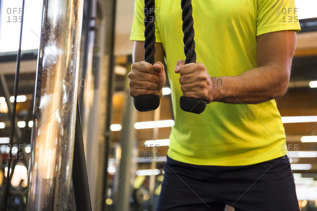 Faceless shot of sportsman working out with exerciser and training triceps