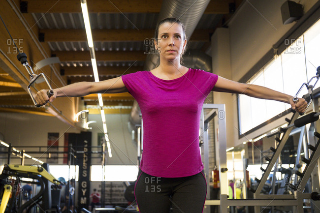 Concentrated sportswoman doing chest cable flys in machine