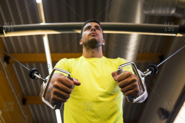 Man in sportswear doing exercises while using exercise machine in gym