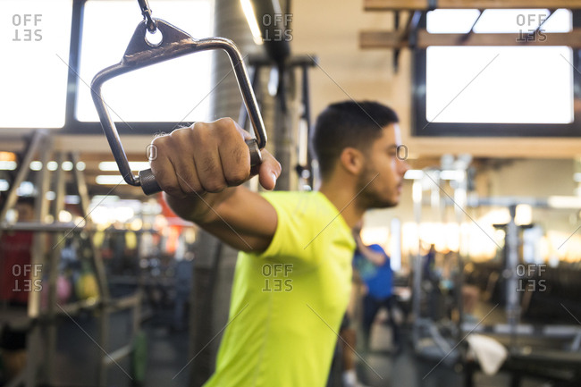 Side view of sportive muscular man looking forward while doing chest cable flys