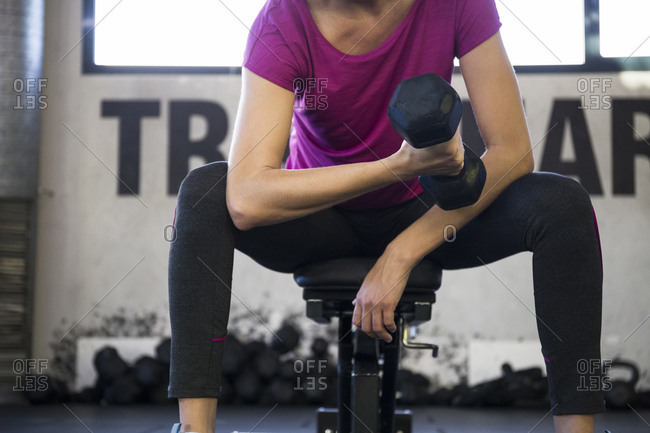 Faceless shot of sportswoman sitting on gym bench lifting dumbbell and training bicep