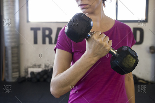 Faceless shot of sportswoman in pink holding dumbbell training bicep in gym