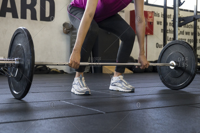 Crop shot of sportswoman on pose preparing to start deadlifting holding barbell on floor