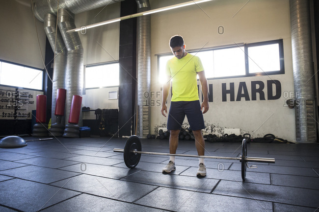 Man in bright T-shirt preparing to lift heavy barbell in gym