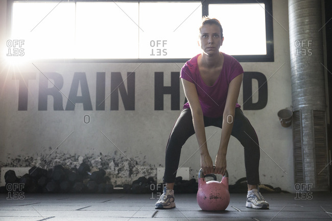 Young determined woman in sportswoman looking forward while preparing to lift kettlebell