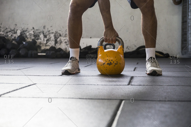 Crop shot of sportsman standing on rubber floor in gym ready to lift heavy kettlebell