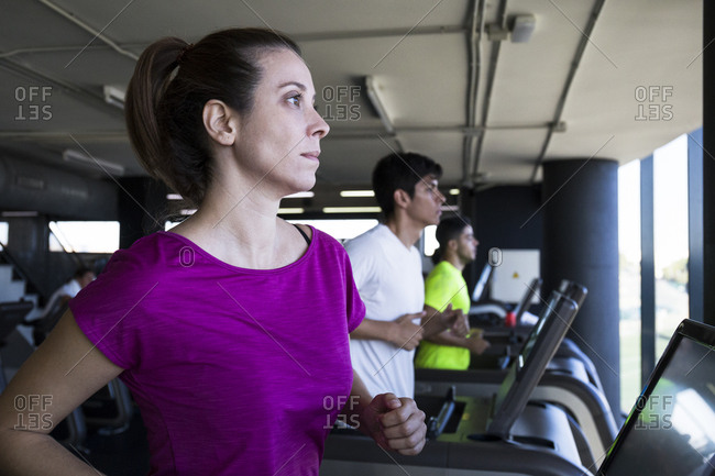 Row of treadmills in gym with people training cardio and running with confidence