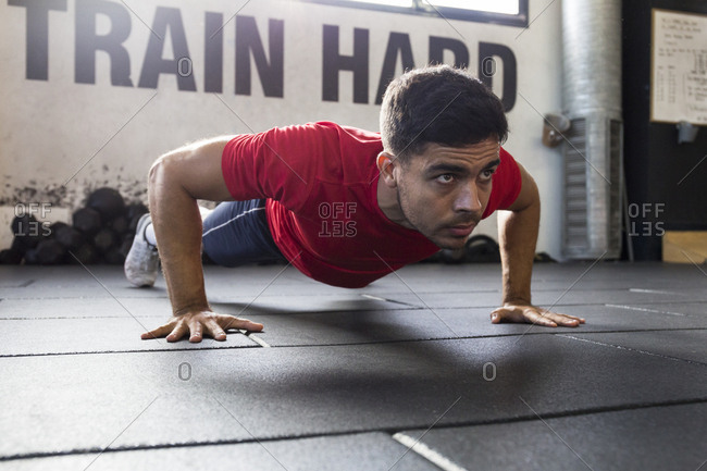 Sportive man looking forward with concentration while doing push-ups on floor of modern gym