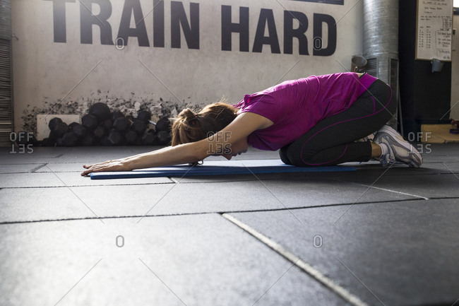Young woman in sportswear breathing deep while stretching muscles sitting on mat and training