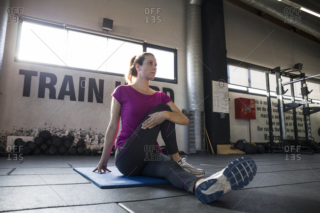 Concentrated sportswoman sitting on mat in spacious gym and stretching muscles of body looking away