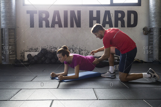 Personal trainer helping woman to perform plank exercise for abdomen working out together